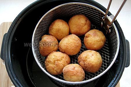Пончики выкладываем в корзину для фритюра или на бумажное полотенце, чтобы избавиться от излишков масла.