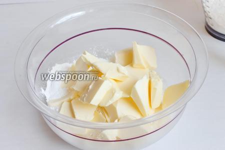 Насыпаем в чашку муки немного, добавим сахар остальной, разрыхлитель. И порежем масло.