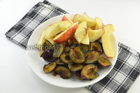 Вымыть яблоки и сливы. У слив удалить косточку и разрезать их пополам. Яблоки разрезать на 8-10 частей и удалить семенное гнездо.