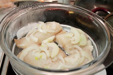 На поверхность рыбы разложить полукольца лука и готовить пикшу на пару 20 минут при слабом кипении, через 10 минут добавив лавровый лист.