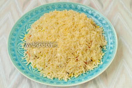 Твёрдый сыр натереть на тёрке, половину сыра отложить. Обсыпать салат полностью сыром.