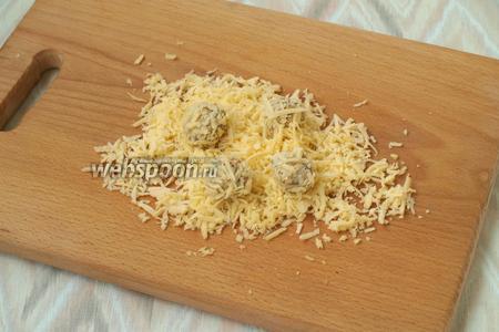Из подготовленной массы скатать небольшие шарики и обвалять их в оставшемся сыре.