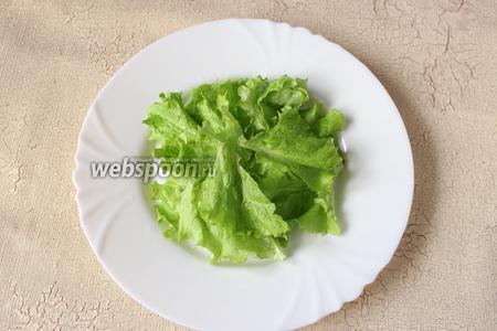 Готовим салат к подаче. На порционную тарелку выкладываем горкой листья салата.