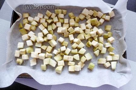 На противень постелем пергамент и разложим кубики баклажана в 1 слой. Солить и сбрызгивать маслом не надо!
