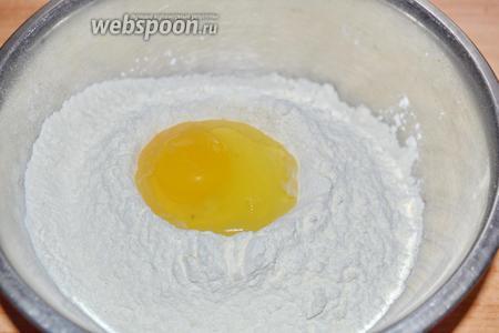 Всыпать в миску 400 г муки, горкой, и перемешать с солью (0,5 ч. л.), сделать небольшое углубление и вбить 4 яйца.