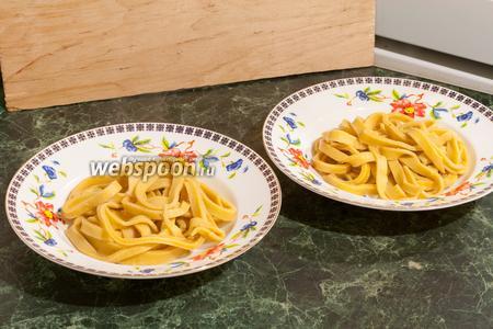 В порционные тарелки выкладываем готовую лапшу.
