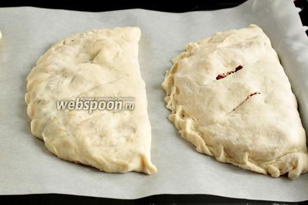 Закрепить края, формируя плоский пирожок. Таким образом слепить 3 лепёшки. Выложить кальцоне на противень, сделать по центру 2-3 надреза и поставить выпекать при 180°С, примерно 20 минут, до румяного цвета.