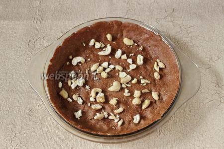 100 г теста выкладываем в форму, распределяем его, делаем бортики. Посыпаем тесто рубленными орехами кешью (20 г). Выпекаем корж 10 минут.