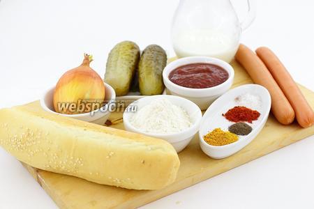 Для приготовления возьмите такие продукты: булочки для хот-догов, сосиски венские, кетчуп, горчицу, солёные огурцы, лук репчатый, муку, куркуму, паприку молотую, соль, чёрный перец, молотый чеснок, масло подсолнечное.