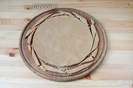 Сухие края медовых коржей обрезаем ножом. Они потом понадобятся для обсыпки.