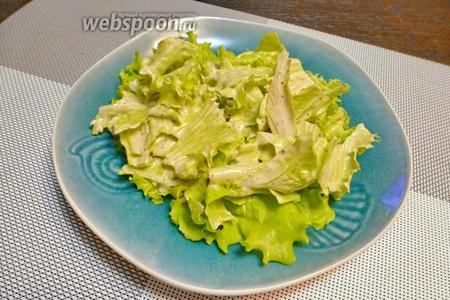 Собираем салат. В порционную тарелку выкладываем листья салата с соусом.