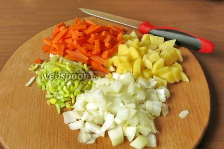 Нарезаем овощи: 1 морковь, 1 лук, 2 картофелины и 20 г лука-порея.