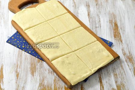 Размороженное тесто раскатать до толщины 2 мм и разрезать на квадраты, которые по размеру подходят к ячейкам вашей бутербродницы.