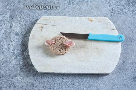 В хлебной заготовке, с 2 сторон, делаем надрезы (в глубину — почти до конца) и вставляем в них уши тыльной стороной ножа, согнув по оси.