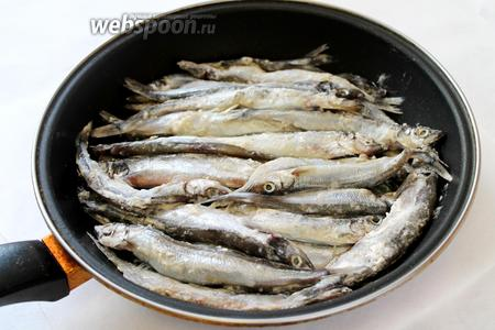 Выложить на лук запанированную в муке рыбу. Поставить на плиту.