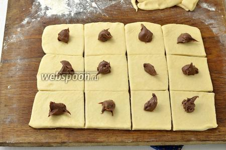 Раскатать тесто толщиной 0,6-0,7 см и нарезать квадратами со стороной 4-5 см. На середину каждого квадрата выложить 1 неполную чайную ложку начинки.