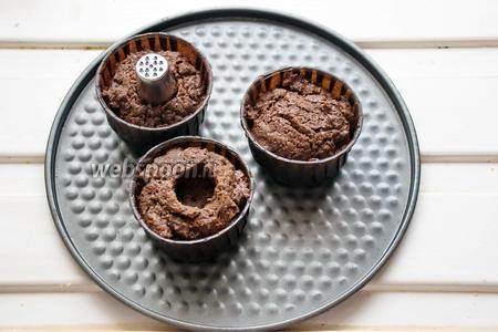 Плунжером (или как у меня — самой большой по диаметру насадкой, вернее, обратной её стороной) выдавливаем в кексах дырочки, вынимая из них тесто. Его можно съесть, а можно, измельчив, добавить в крем.