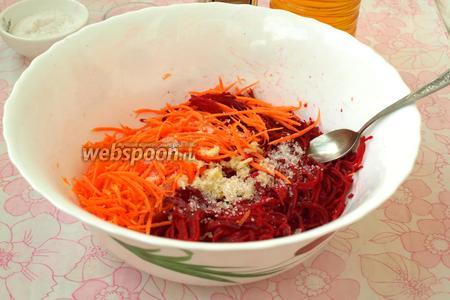 К свёкле с морковью добавить 0,5 ч. л. соли и 0,5 ч. л. сахара, также с помощью чесночницы выдавить в салат чеснок.