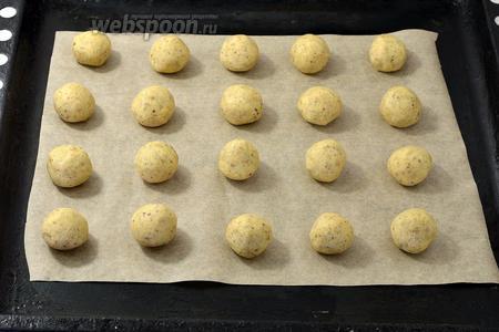 Разделить тесто на небольшие кусочки размером с грецкий орех. Скатать кусочки  в шарики и разложить на противне с пергаментной бумагой, соблюдая между ними расстояние.