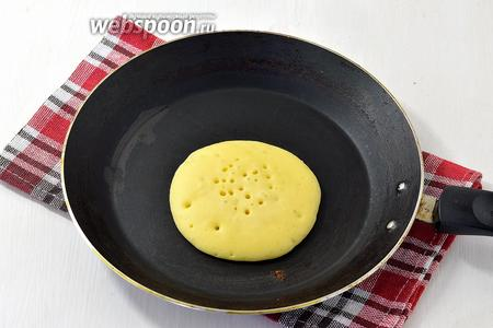 В центр сухой, разогретой сковороды выкладывать по половнике теста. Сразу накрыть крышкой и подождать, пока сверху появятся пузырки воздуха. Перевернуть на вторую сторону и дожарить панкейк.