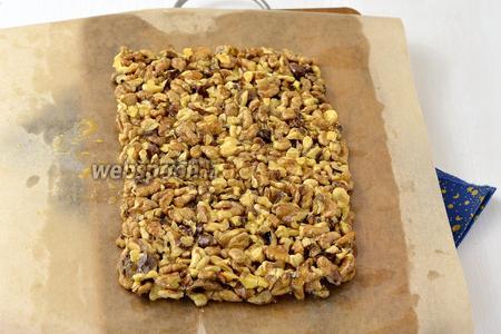 Пергаментную бумагу смазать тонким слоем растительного масла и выложить горячую ореховую массу на пергамент. Разровнять и придать форму. Толщина пласта должна быть приблизительно 1 см. Отправить в холодильник на 1 час.