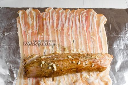 Расстелить на столе 2 слоя фольги, по размеру длины кусочков бекона. Разложить кусочки бекона (200 г) по фольге. Выложить на крайнюю часть бекона подготовленную вырезку. Посолить (2 щепотки), поперчить (2 щепотки), посыпать кусочками рубленого чеснока (3 зубчика).