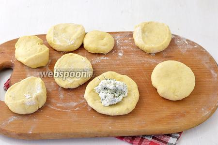 Разделить тесто на небольшие кусочки. Сформировать лепёшки. На середину каждой выложить 1 столовую ложку начинки. Тщательно защипнуть и сформировать пирожки.