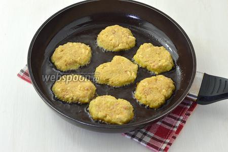 Разогреть сковороду с подсолнечным маслом (100 мл). Выкладывать драники в виде небольших лепёшек, соблюдая между ними расстояние. Жарить на одной стороне до золотистой корочки, а потом на второй.