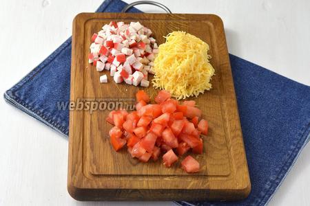 3 помидора нарезать мелким кубиком и слить выделившийся сок. Крабовые палочки (200 г) нарезать мелким кубиком. Сыр (200 г) натереть на мелкой тёрке.
