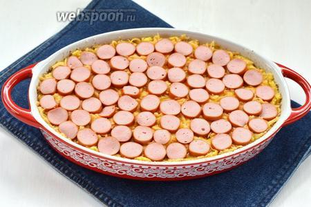 Сосиски (5 штук) нарезать кружочками и равномерно разложить сверху, немного вжав их в картофель.