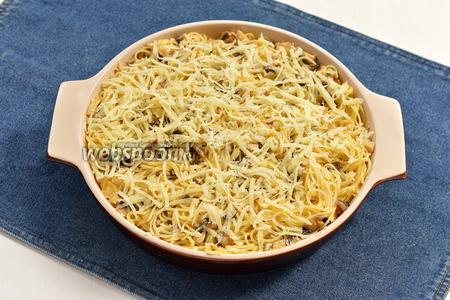 Форму для запекания смазать сливочным маслом и посыпать сухарями. Выложить массу в форму, полить молочно-яичной смесью и равномерно посыпать остальным натёртым сыром (50 г).