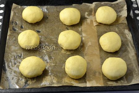 Из подошедшего теста сформировать небольшие булочки весом 95-100 г, выложить их на противень с пергаментом и оставить на 20 минут.