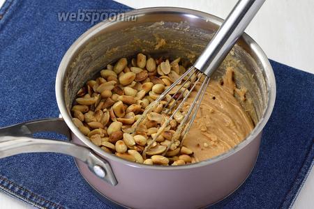 В загустевшую массу быстро вмешать подготовленный арахис (140 мл) и ванильный сахар (10 г).