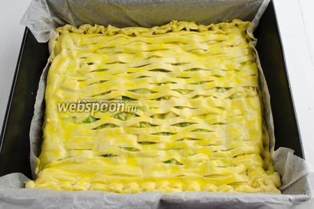 Закрыть пирог сверху подготовленным листом. Закрепить края. Смазать верхнюю поверхность пирога оставшейся яичной смесью. Поставить противень в горячую духовку.