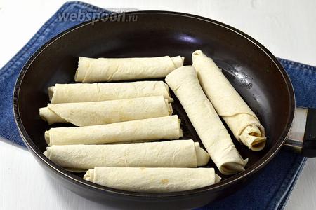 Разогреть сковороду с подсолнечным маслом (3 ст. л.) и выложить на неё палочки швом вниз. Обжарить палочки с двух сторон до золотистого цвета.