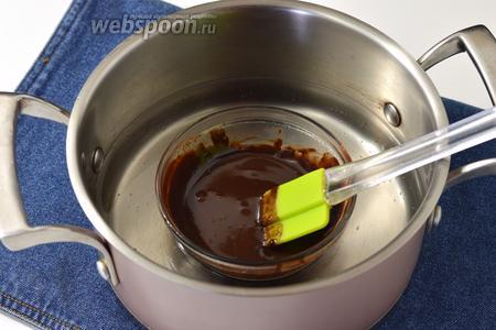 Поместить мисочку с шоколадом в кастрюлю с водой (0,5 л), нагретой до 45°С. Вода должна доходить приблизительно до середины мисочки. Помешивать массу кулинарной лопаткой, пока шоколад не растает на 2/3. После этого вынуть мисочку из воды и продолжать помешивать. Шоколад очень быстро растопится весь.