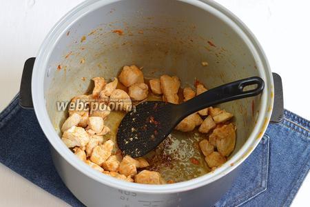 В чашу, освобождённую от овощей, выложить порезанное на небольшие кусочки куриное филе (300 г) и 2 столовых ложки подсолнечного масла. Жарить 6-7 минут, помешивая.