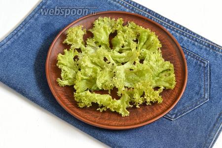 Листья салата (50 г) порвать руками и выложить на блюдо.