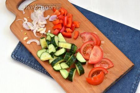 Лук (0,5 шт.) очистить и нарезать полукольцами, перец (0,5 шт.) очистить от семян и нарезать кусочками, 2 помидора нарезать дольками, а 2 огурца крупными кусочками.