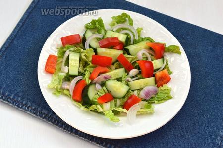 На блюдо выложить пекинскую капусту. Сверху разложить перец, огурцы и лук. Приправить овощи солью (1 г).