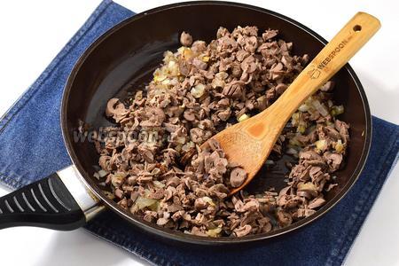 Мелко порезать куриные сердечки и всыпать их к луку. Приправить по вкусу солью и перцем. Прогреть 2-3 минуты.