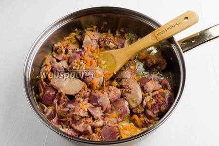К овощам добавить подготовленную печень. Жарить печень, помешивая. Закрыть сковороду крышкой. Томить печень с овощами на тихом огне в течение 20 минут.