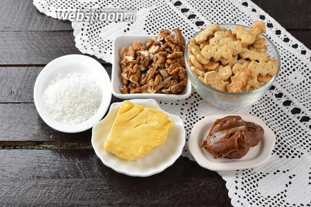 Для работы нам понадобится готовое печенье «Хрустик с маком», орехи грецкие, сливочное масло, кокосовая стружка, варёное сгущённое молоко. Вот и все ингредиенты для простого рецепта муравейника без выпечки.