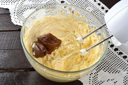 Порциями добавлять варёное сгущённое молоко (450 г), постоянно взбивая.