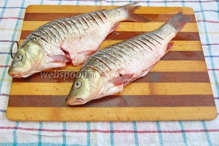 Рыбу (400 г) посолить (3 щепотки), сделать надрезы на теле и оставить на 10 минут, чтобы она просолилась.