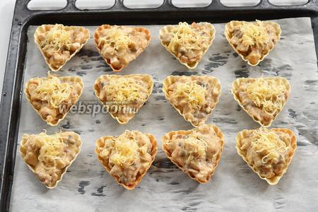 Разложить смесь по тарталеткам (12 штук). Сверху присыпать натёртым твёрдым сыром (100 г).