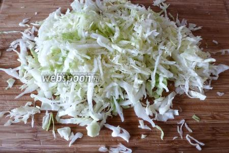 Молодую и сочную капусту (200 г) нашинкуем потоньше, посыплем сахаром (1 щепотка), перцем (1 щепотка) и немного помнём пальцами.