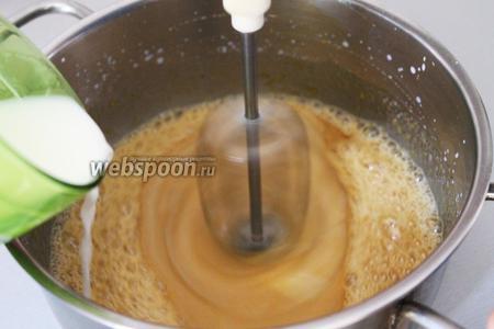 Влейте тонкой струйкой молоко (250 мл) и продолжайте взбивать.