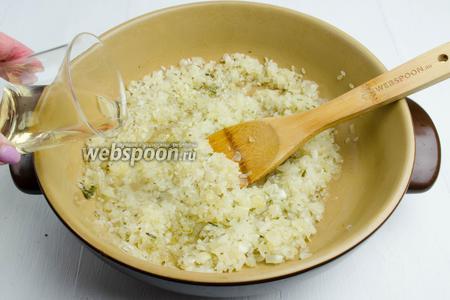 Рис должен очень быстро пропитаться оливковым маслом. Через 1 минуту влить вино (100 мл). Подержать на огне, слегка помешивая, до выпаривания алкоголя.