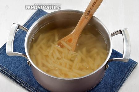 Отварить макароны (200 г) в слегка солёной воде почти до готовности.